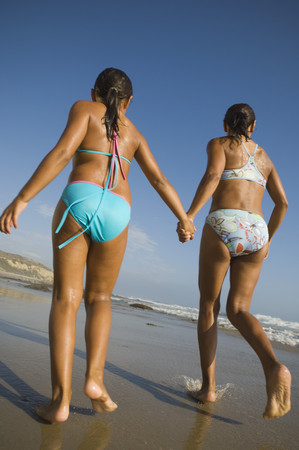 Hispanic mother and daughter running at beach