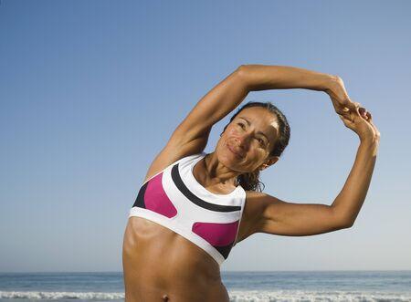 Hispanic woman stretching at beach