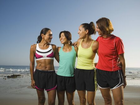 front raise: Multi-ethnic female runners at beach LANG_EVOIMAGES