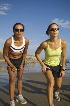 commencing: Hispanic female runners racing at beach LANG_EVOIMAGES
