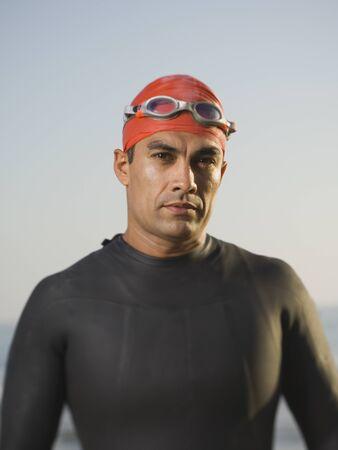 bathingsuit: Hispanic man wearing wetsuit and goggles
