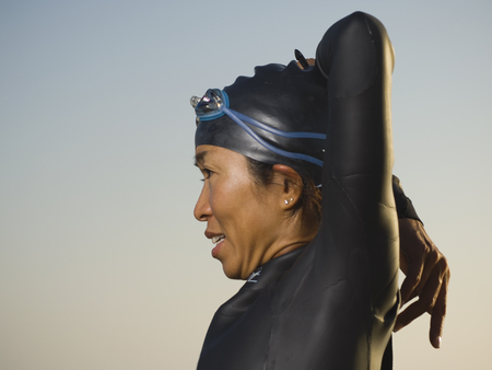 nite: Asian woman stretching in wetsuit and goggles
