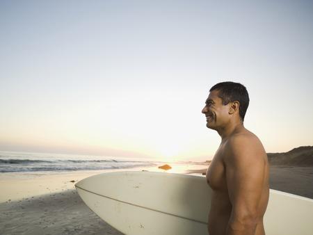 togs: Hispanic man holding surfboard