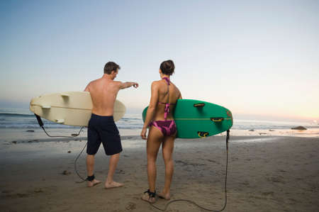 smooching: Multi-ethnic couple holding surfboards LANG_EVOIMAGES