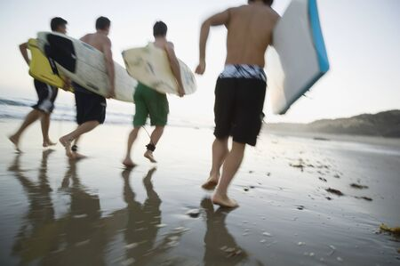Multi-ethnic men running with surfboards