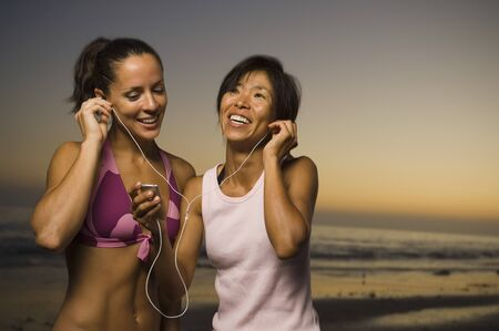 nite: Multi-ethnic friends listening to same mp3 player LANG_EVOIMAGES