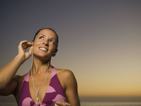 bathingsuit: Hispanic woman listening to mp3 player