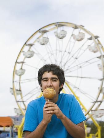 teenaged boy: Mixed Race teenaged boy eating candied apple