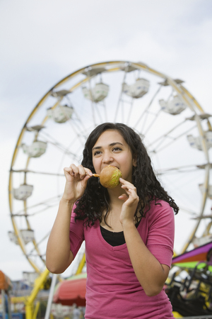 1 person: Mixed Race teenaged girl eating candied apple LANG_EVOIMAGES