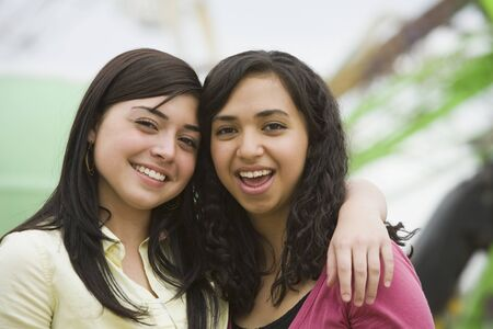 teenaged girls: Multi-ethnic teenaged girls hugging LANG_EVOIMAGES