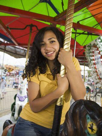 teenaged girl: Mixed Race teenaged girl on carousel horse LANG_EVOIMAGES