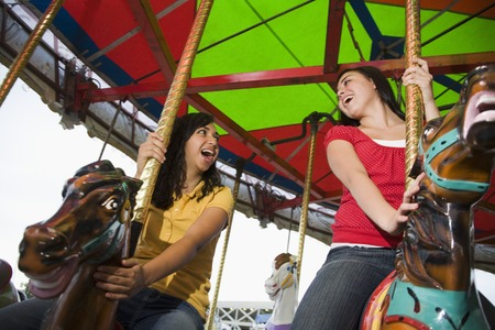 teenaged girls: Mixed Race teenaged girls on carousel horse LANG_EVOIMAGES