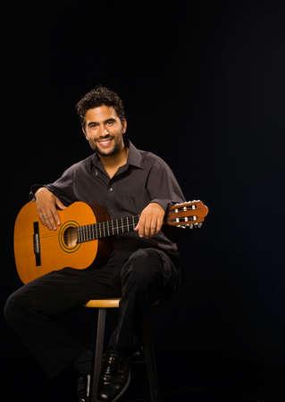 prevailing: Hispanic man holding acoustic guitar