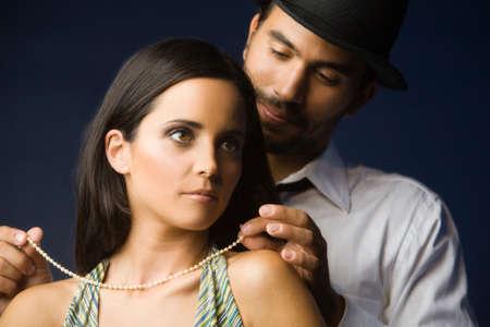 honeymooner: Hispanic man fastening wife's necklace
