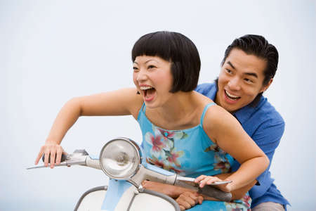 honeymooner: Asian couple riding motor scooter LANG_EVOIMAGES