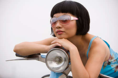 attired: Asian woman sitting on motor scooter