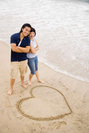 Asian couple next to heart in sand Stock Photo