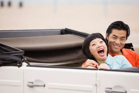 honeymooner: Asian couple laughing in convertible LANG_EVOIMAGES