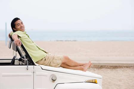 honeymooner: Asian man laying on car hood LANG_EVOIMAGES