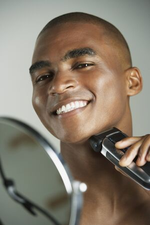 one mid adult man only: African man shaving with electric razor