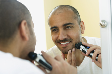 electric razor: Middle Eastern man shaving with electric razor