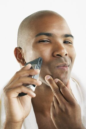 electric razor: African American man shaving face with electric razor