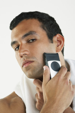 cardboard only: Hispanic man shaving face with electric razor LANG_EVOIMAGES