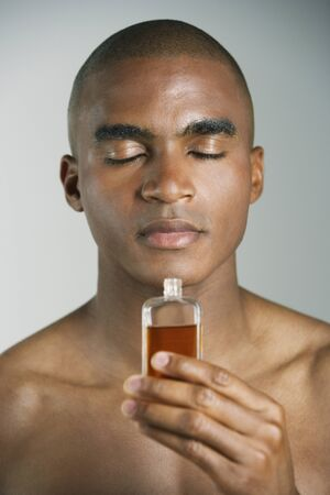 mischievious: African man smelling cologne LANG_EVOIMAGES