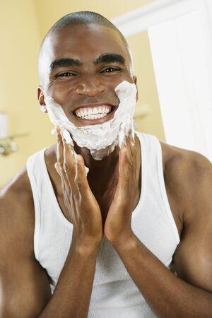 1 man only: African man applying shaving cream LANG_EVOIMAGES