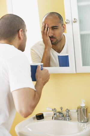one mid adult man only: Middle Eastern man looking in mirror