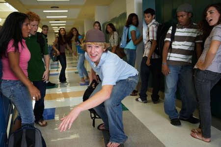 teenaged boy: Teenaged boy riding skateboard in school hallway