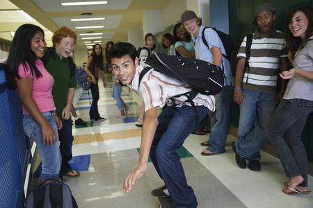 teenaged boy: Hispanic teenaged boy riding skateboard in school hallway
