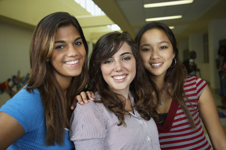 teenage girl: Multi-ethnic teenaged girls hugging in school hallway