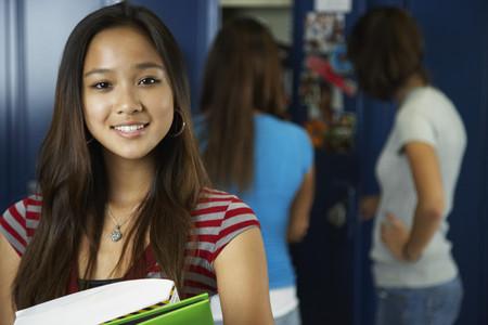 teenaged girl: Asian teenaged girl in front of school lockers LANG_EVOIMAGES