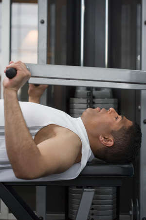 weight machine: Hispanic man using weight machine LANG_EVOIMAGES