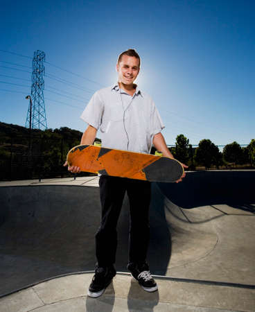 tugging: Portuguese young man holding skateboard