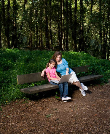 age 5: Hispanic mother and daughter looking at laptop in woods