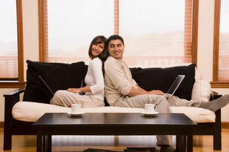 couple on couch: Hispanic couple sitting back to back on sofa