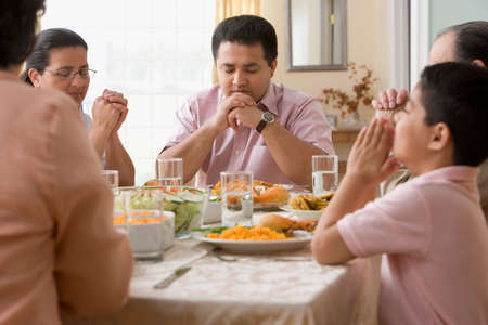 family praying: Familia hispana orando a mesa