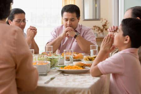 orando: Familia hispana orando a mesa