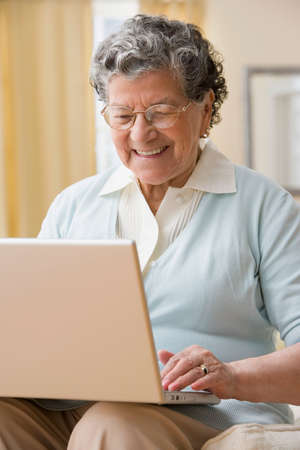 jeopardizing: Senior Hispanic woman typing on laptop