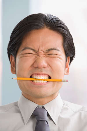 acknowledging: Asian businessman biting on pencil