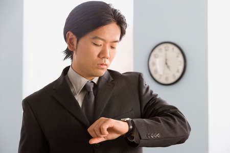 motioning: Asian businessman looking at wristwatch
