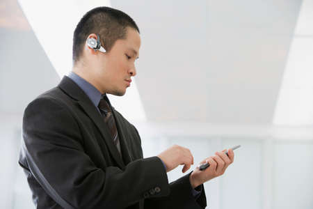 handsfree device: Asian businessman talking on hands-free device LANG_EVOIMAGES
