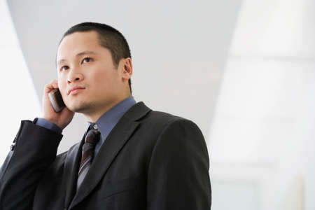 acknowledging: Asian businessman talking on cell phone