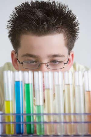 hindering: Hispanic boy looking at vials of liquid
