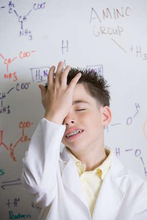 Hispanic boy in front of molecular formulae on whiteboard