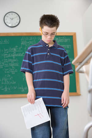 shaming: Hispanic boy holding school paper with F grade LANG_EVOIMAGES