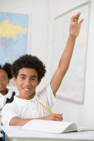 blabbing: Hispanic boy with hand raised in class LANG_EVOIMAGES
