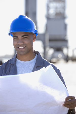 drydock: African American male construction worker holding blueprints